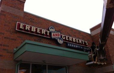"""A worker on a crane installs an """"Erbert and Gerbert's Sandwich Shop"""" sign on a new franchise location."""