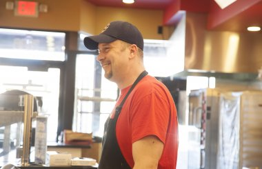 A smiling employee of an Erbert and Gerbert's franchise stands behind the serving and prep counter.