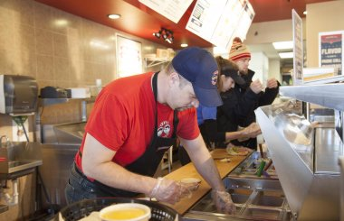 Two employees at an Erbert and Gerbert's location make sandwiches behind the counter as a third bags sandwiches and prepares to take them on a delivery.
