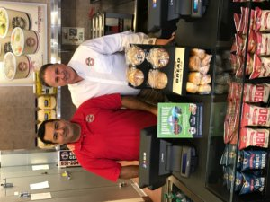 Franchisee Manuel Pizaño-Carlo poses with President and CEO Eric Wolfe behind the register at the newly opened 100th Erbert & Gerbert's location.